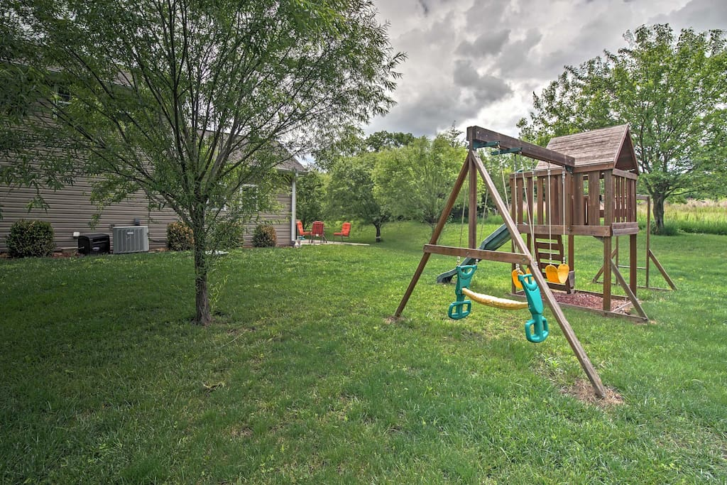 A large yard with a playset creates the perfect space for kids to play.