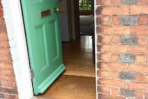 Front door entrance with small step up into house. Shoe scraper visible bottom right.