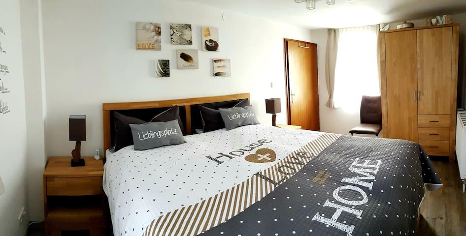 Das Wohlfühl-Schlafzimmer ist mit einem  Vollholz-Boxspring-Doppelbett und einem Flatscreen-TV ausgestattet. Geräumiger Kleiderschrank. Helligkeit und Lichtwärme sind veränderbar. Somit kannst du dir deine Wohlfühlatmosphäre schaffen.   -1.OG-