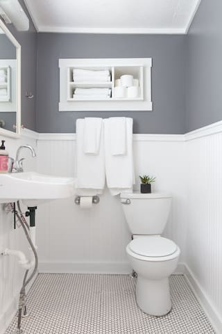 Newly-refreshed bathroom with bright white beadboard and vintage white penny tile.