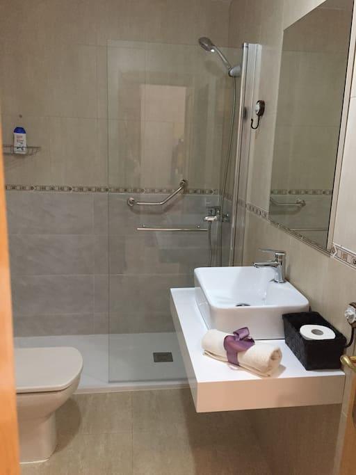 Baño con plato de ducha y mampara abatible para fácil acceso.