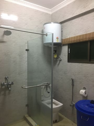 Washroom with hot water, glass partitioned shower.