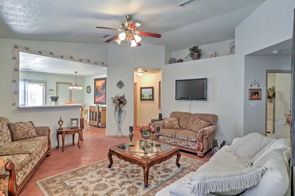 The living room offers comfortable plush seating, ceiling fan, flat-screen TV, and a queen sofa sleeper for flexible sleeping arrangements.