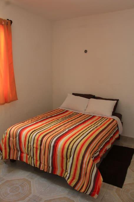Habitación No. 1 con aire acondicionado, tocador, closet y plancha para ropa.