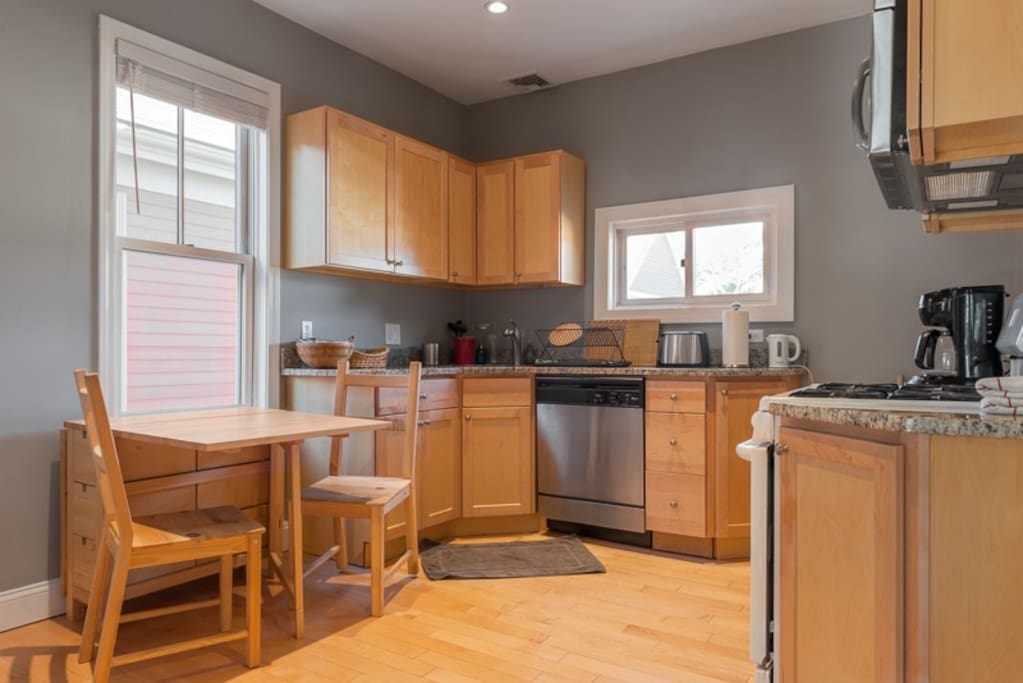 Beautiful kitchen with lots of natural sunlight, hardwood floors, dishwasher, flexible seating arrangements and more.