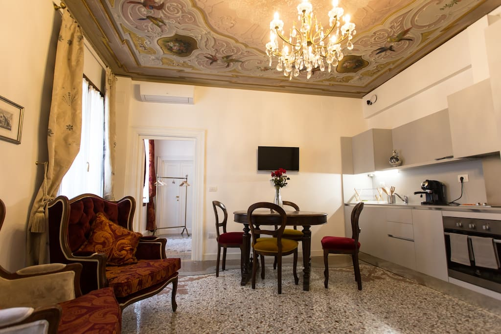 Salone, con cucina open space completamente attrezzata, decorato con uno splendido affresco d'epoca * Lounge area with an open space fully equipped kitchen, decorated with a splendid fresco of the period.