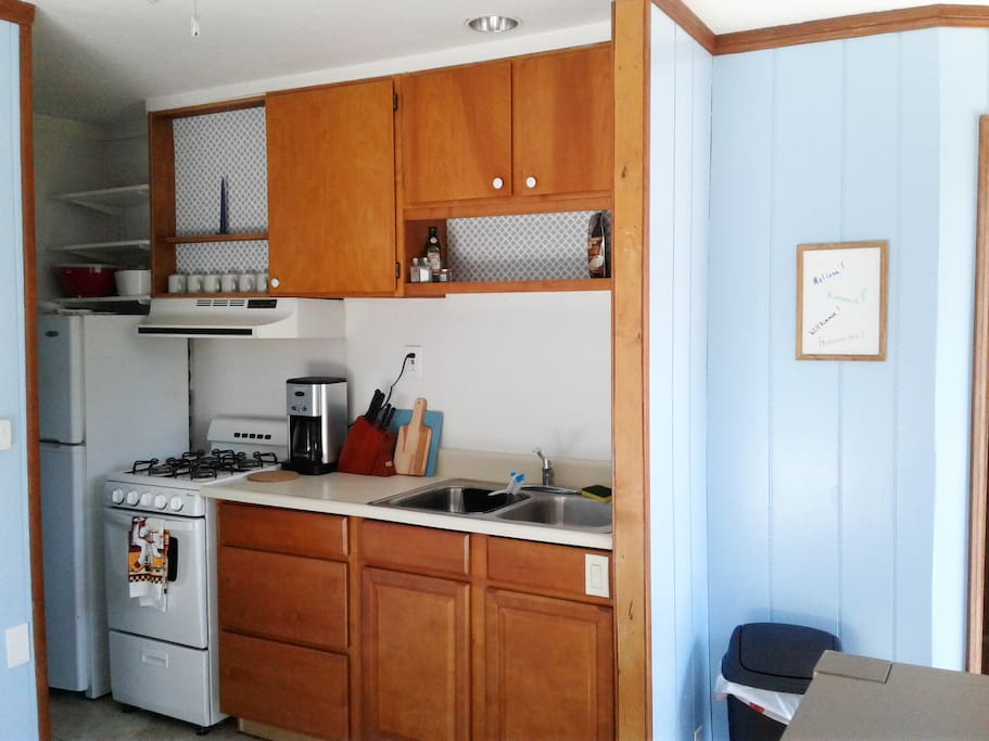 Kitchen with fridge, freezer, gas oven, coffee maker, microwave and basic cooking tools.