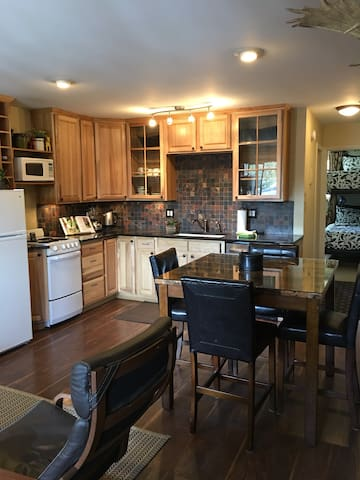 Nicely stocked modern kitchen with granite countertops, dishwasher, fridge and electric stove.