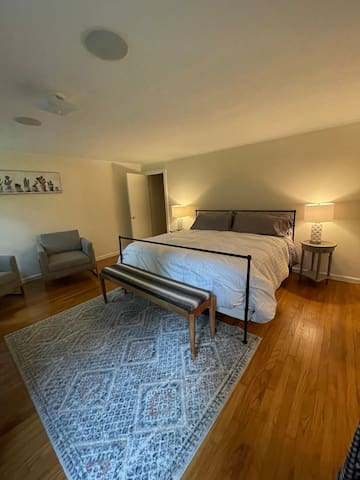 The spacious primary bedroom suite has a king bed, views of the yard and pool and it's own private en-suite bathroom.