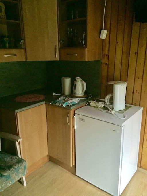 kitchen corner with fridge, water kettle, coffe machine, cups, plates, cutlery etc