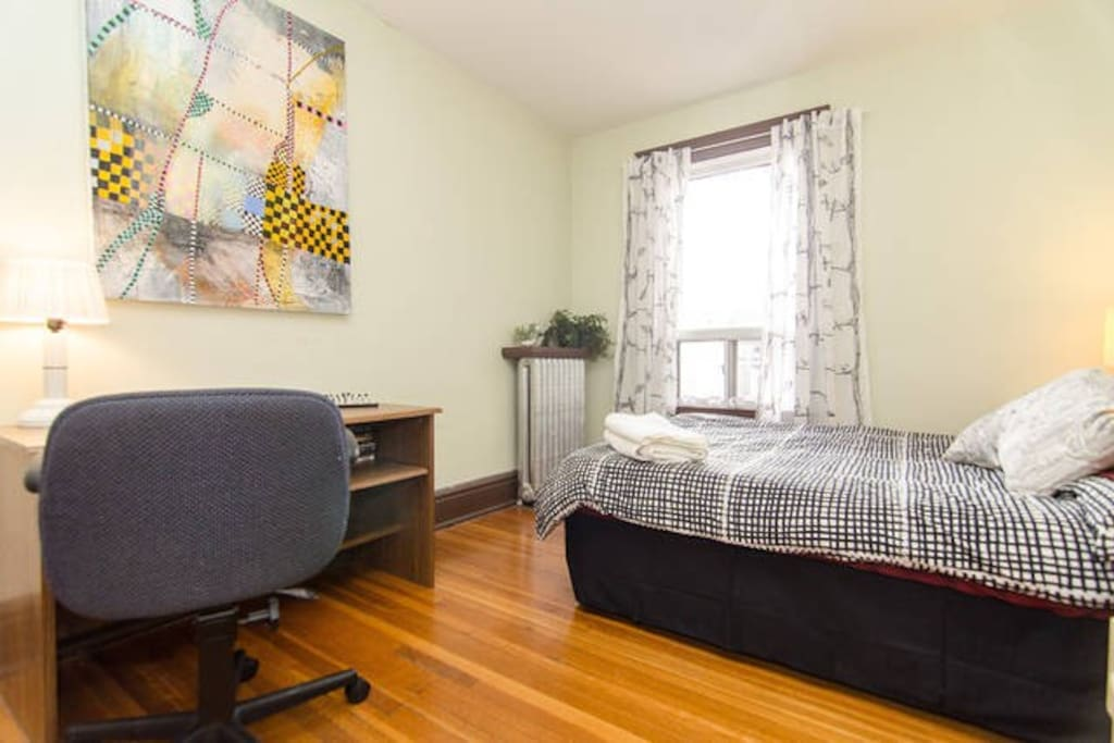 Bedroom has a desk with an office chair.