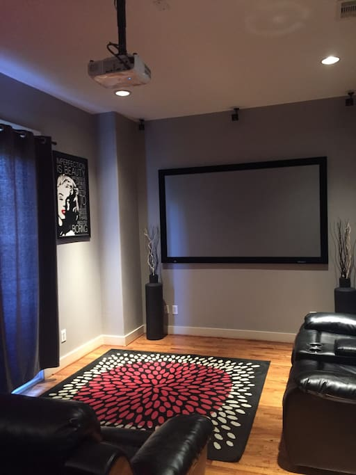 living room with 90 inch projector screen and Bose speakers perfect for movies and to watch the game.