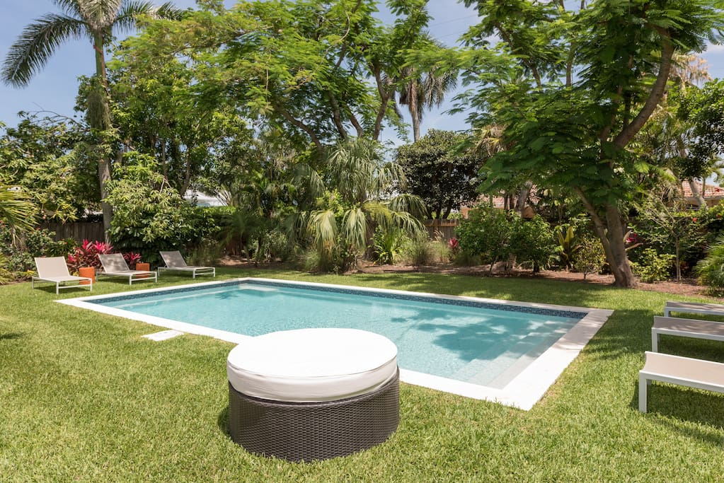 Stone pool surrounded by grass. 6 lounge chairs situated at edge of pool. Ample sun throughout the day with a private enclosed feel and lush landscaping