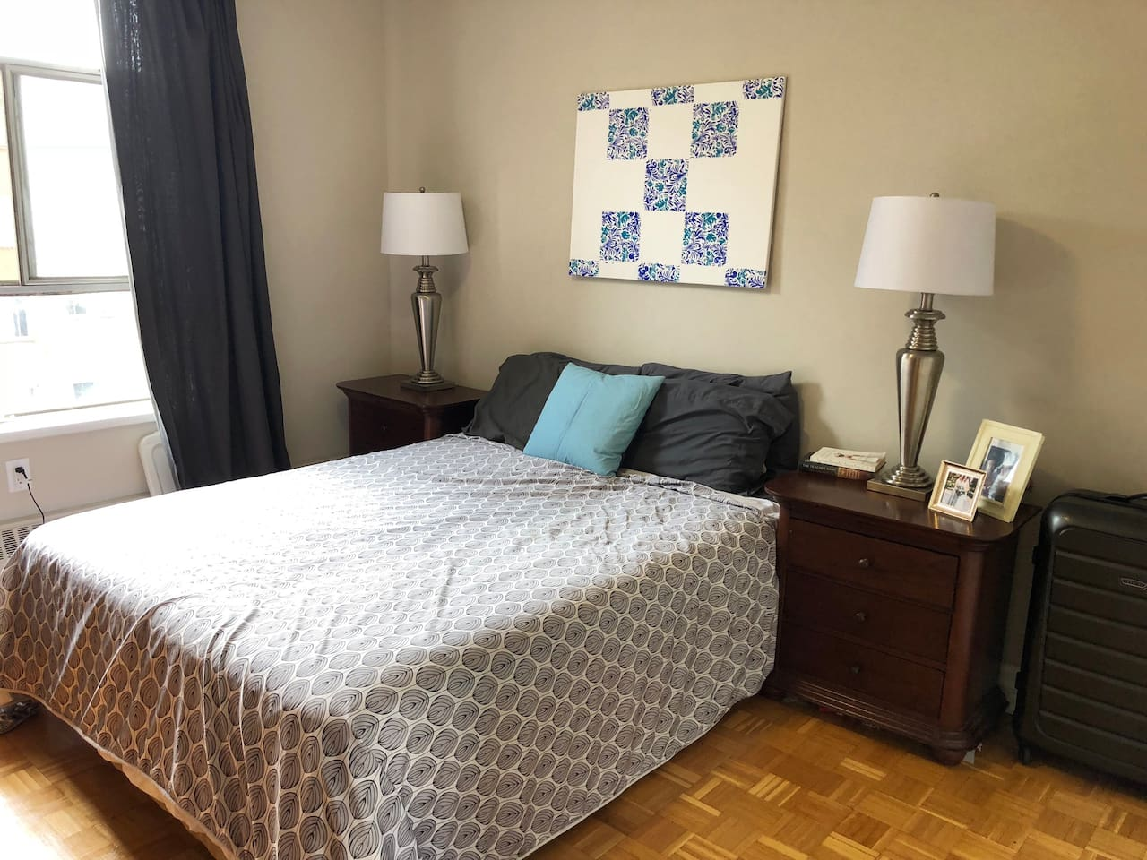 Spacious bedroom with a queen bed, google mini home, and window.