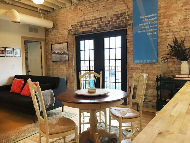 Exposed brick and a french door balcony surround the dining space.