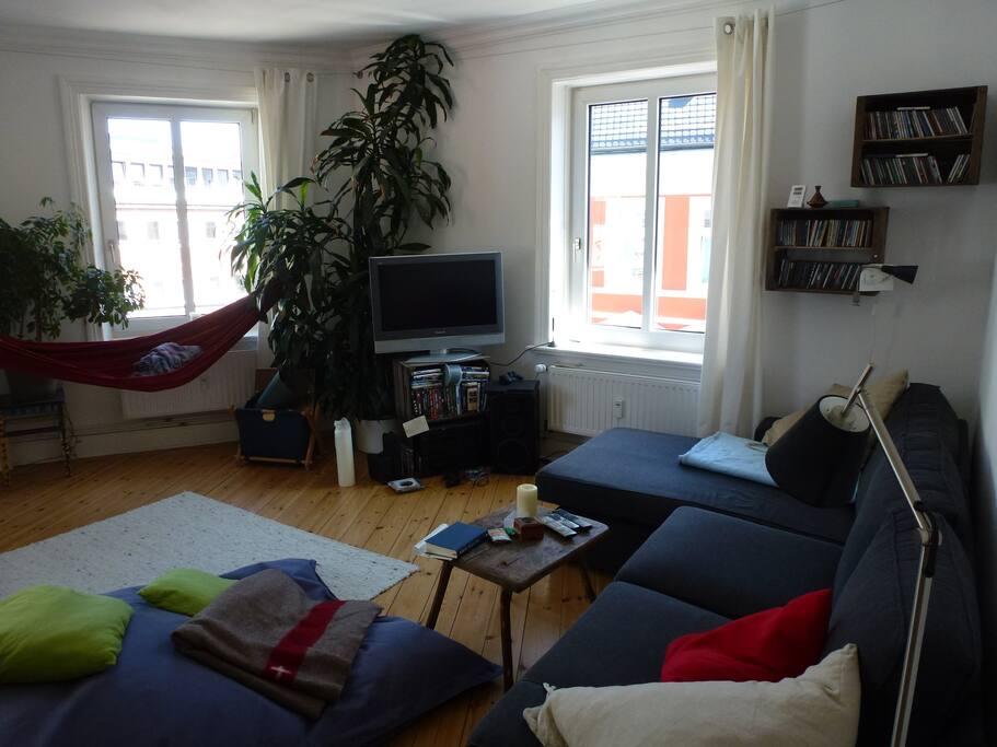 großes Wohnzimmer mit großer Couch und drei Fenstern