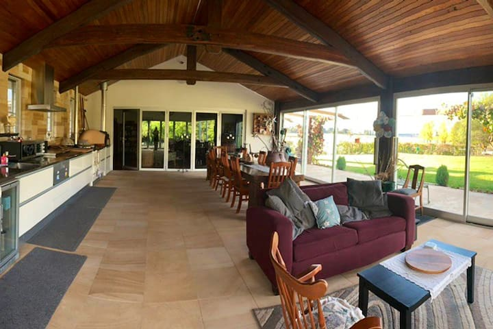 The main  entertaining area, with large windows overlooking the dam and paddocks.  Offers large area with wood fired pizza oven, gas cooktop, microwave, fridge, dishwasher and large dining table.  Sandstone flooring and exposed timber ceiling.