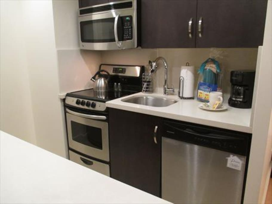 Fully equipped kitchen with stainless steel appliances, pots, pans, and dishes
