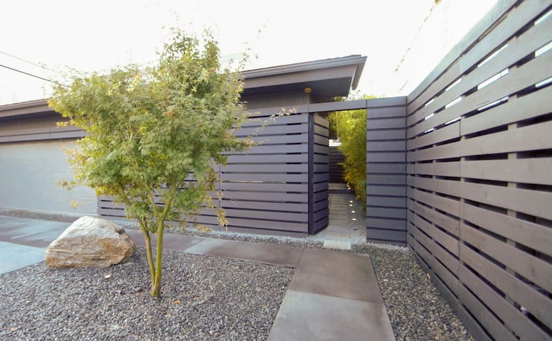 a japanese maple tree sits between the garage and the pedestrian entrance to the ground floor apartment.