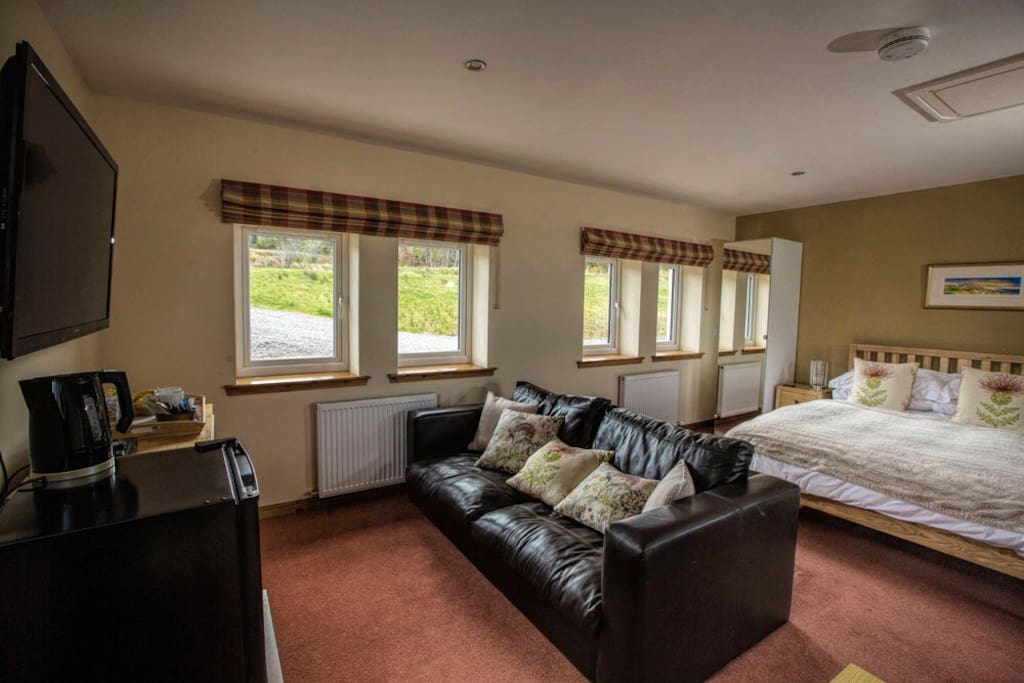 """Room is decorated in a Scottish theme, king size bed, sofa, 50""""Tv, and blue ray DVD player. Fridge with complimentary breakfast."""