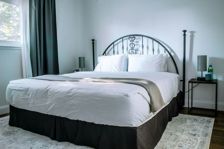 King bedroom with cast iron accents and lux bedding, fit for a king. Touch-on table lights come with USB ports for hassle free charging of devices, and scented candles to lovely-up the mood.