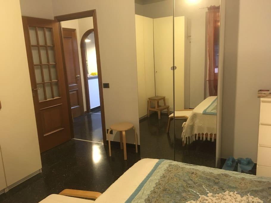 Camera da letto, armadio a specchio e porta sull'ingresso