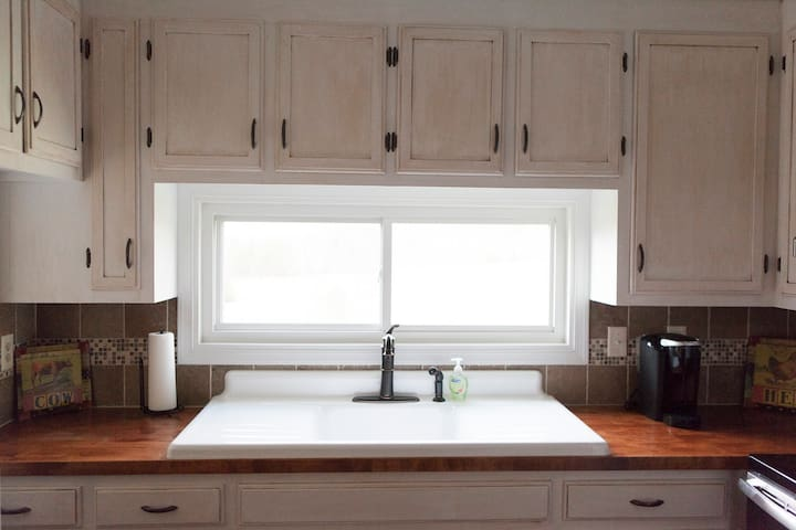 Farmhouse kitchen sink, Keurig, and butcher block countertops.