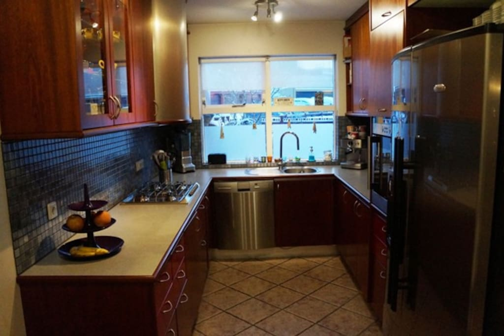The kitchen with dishwasher and a fridge with ice maker.