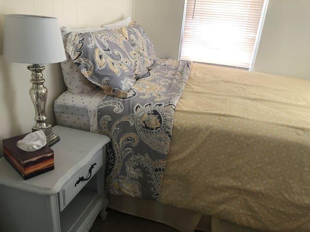 bedroom with queen bed, nightstand lamp and dresser