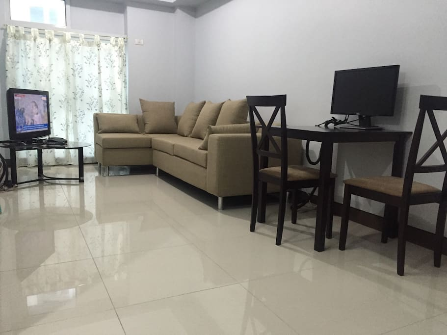 """Living room with 4-seater sofa, 32"""" LCD tv installed with cable tv, and up to 8mbps broadband internet, wifi enabled.   Dining area with dining table for 2."""