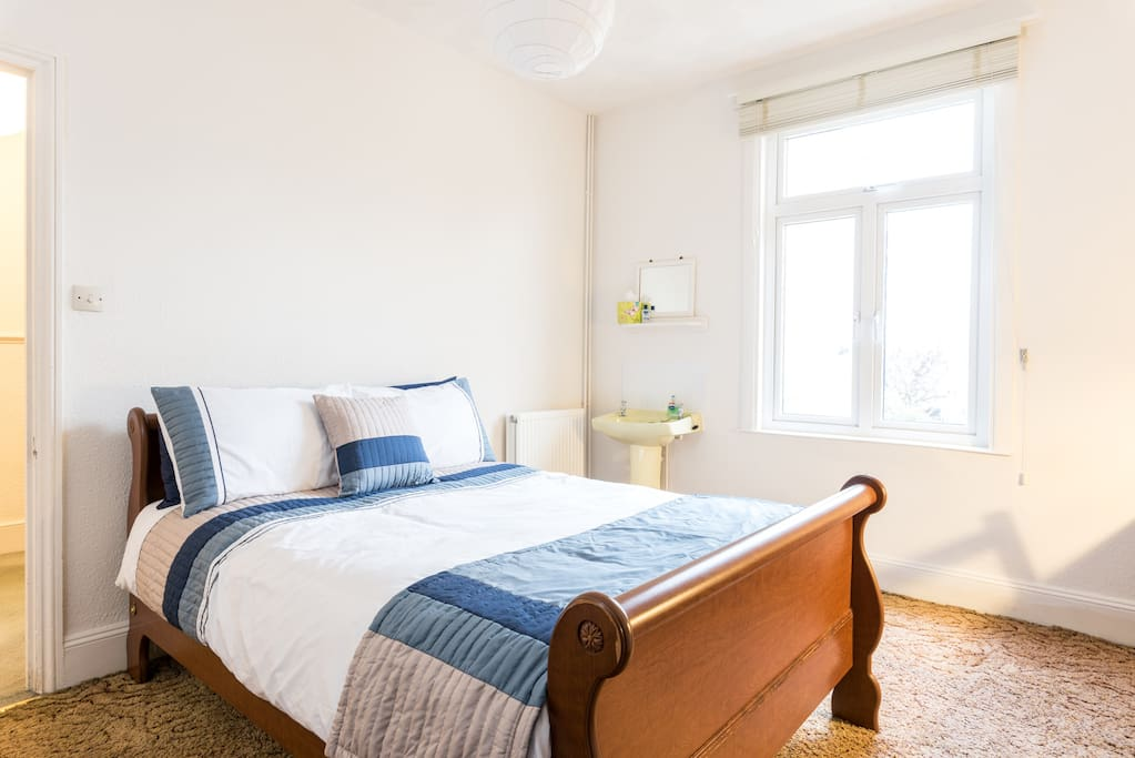 Comfy double bed, convenient washbasin and window on to garden.