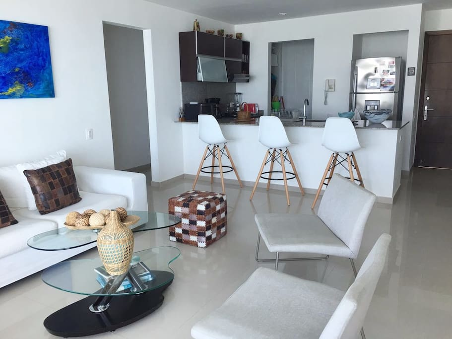 Modern Living Room.  Fully-Equipped Kitchen with barstools  and area to eat . Laundry Area with Washing and Drying Machine. Cocina totalmente equipada con  taburetes y area para comer. Zona de aseo con Lavadora y Secadora