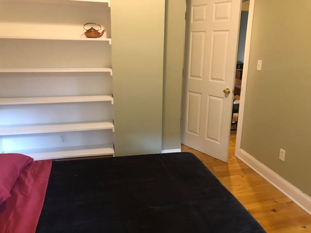 Bedroom hosts a full bed, plenty of shelving, and access to the private balcony and shared backyard.