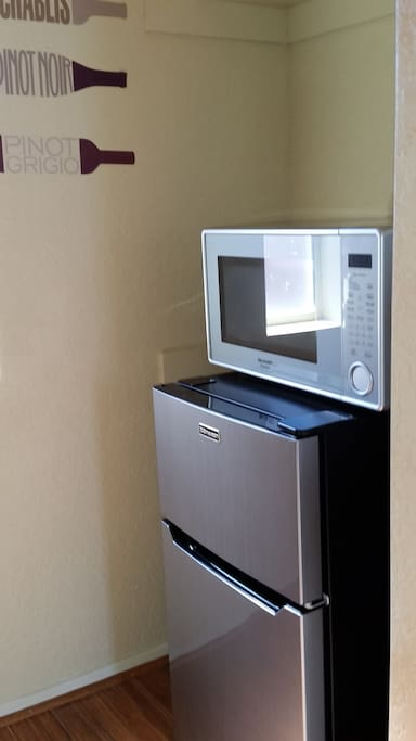 mini refrigerator, coffee maker and microwave along with place setting for 2 people