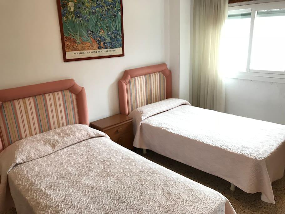 Dormitorio con 2 camas individuales y vistas a la playa .