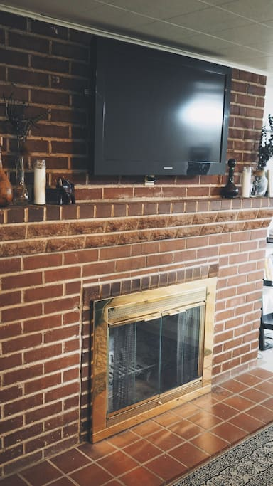 TV with entertainment subscriptions and working fireplace.