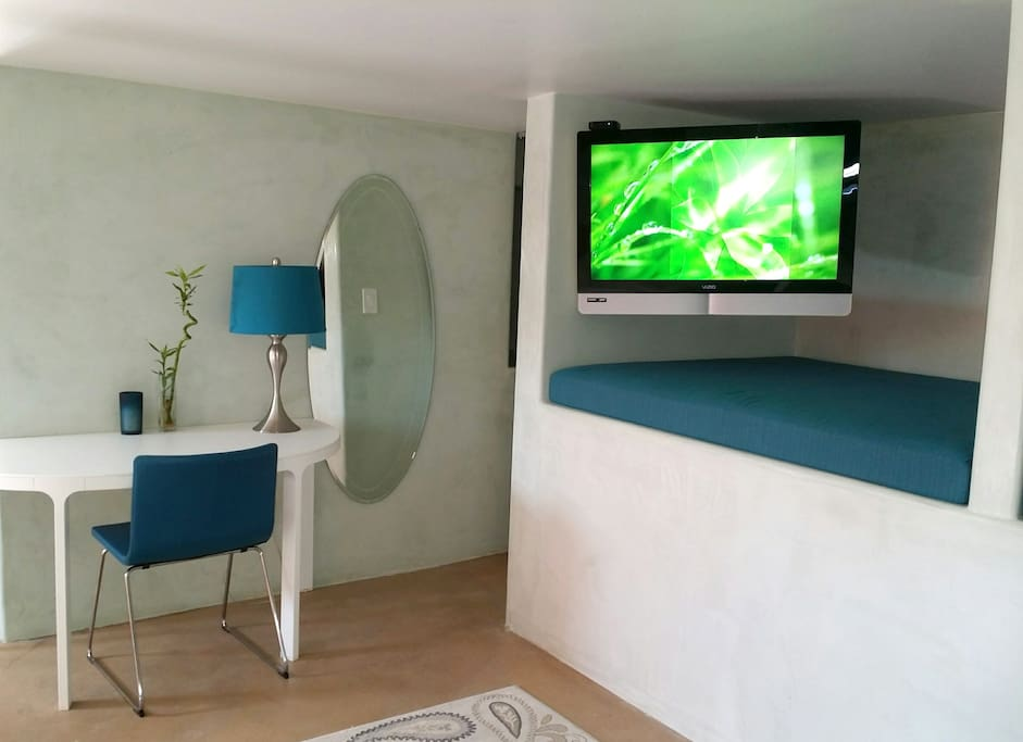 Table, Lounge area with Flat Screen Apple TV and closet with full length mirror.
