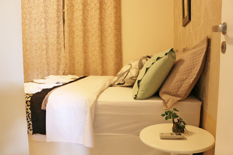 Cama casal,  travesseiro extras, cortina blecaute, ar-condicionado, roupa de cama, toalha, tapete.