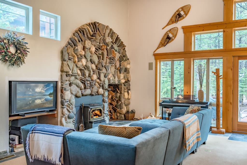 The grand living room features vaulted ceilings, knotty pine accents, and an impressive stone hearth fireplace.