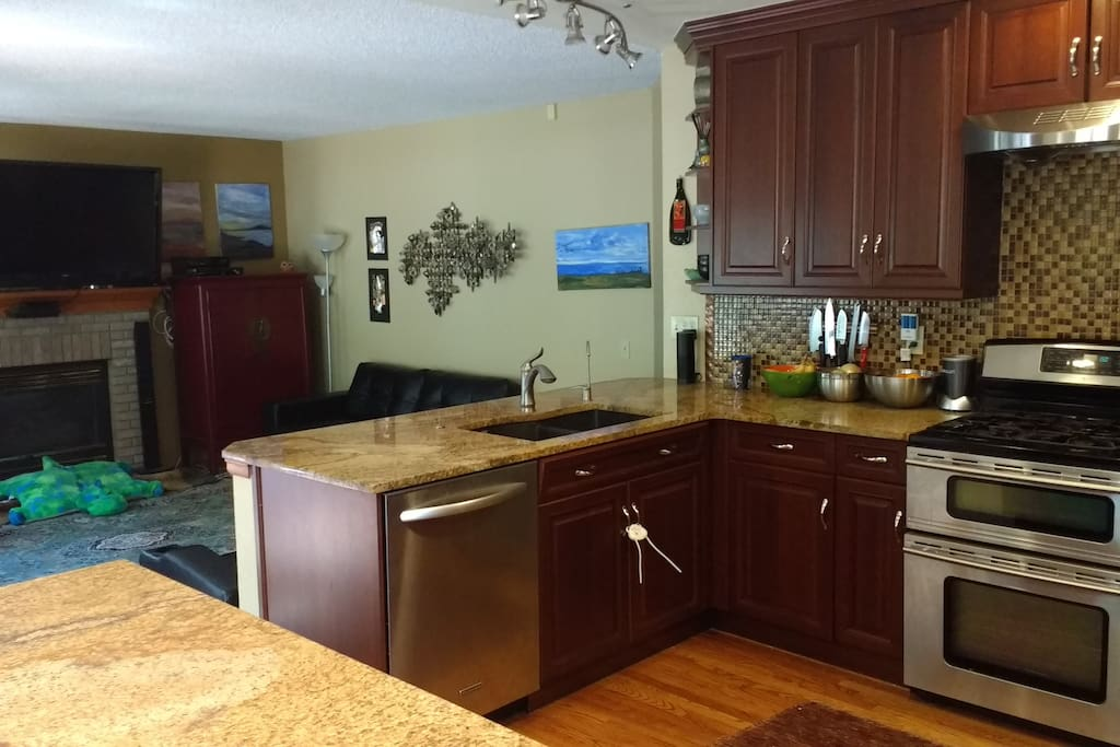 """Modern, updated kitchen uses an open flow concept to the den and a 60"""" television with hi speed wifi"""