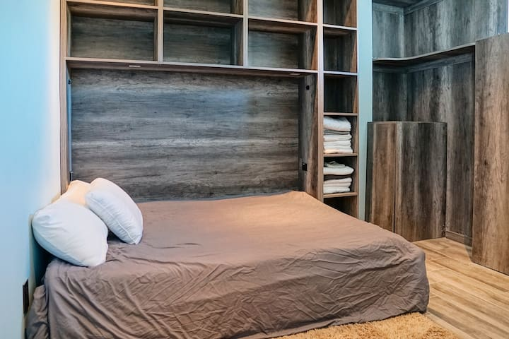 Bedroom 2 contains plenty of shelves for storage as well as a queen sized bed, outfitted with a deluxe memory foam mattress pad.