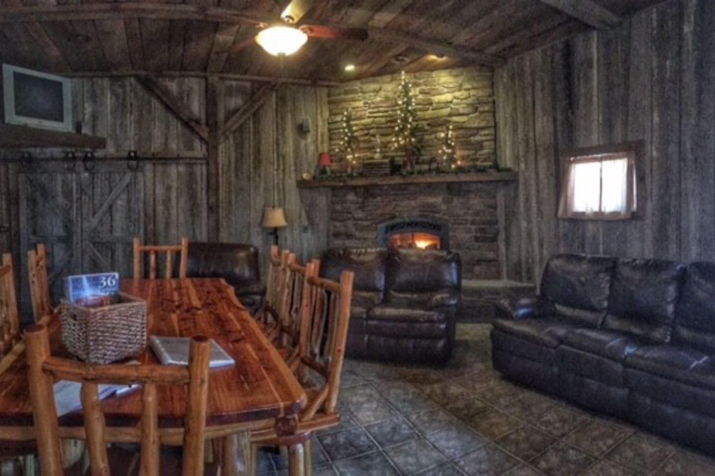 the living room includes leather couches, tables and chairs and a fireplace