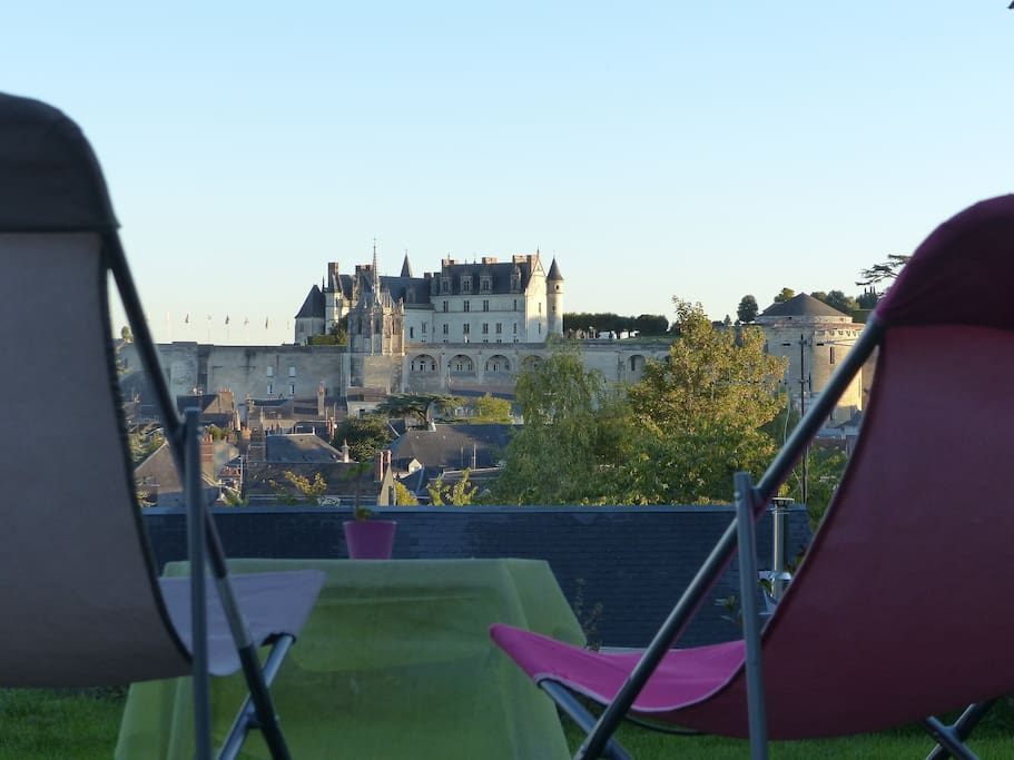 Chaises longues face au château depuis la terrasse du jardin.