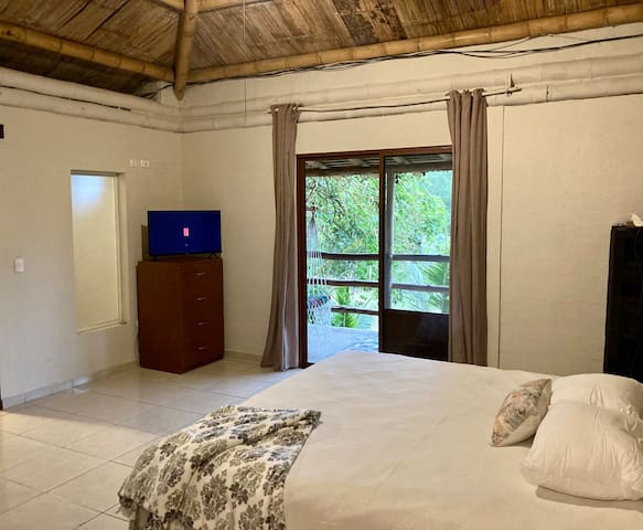 Large bedroom, Queen size Bed, Tv, AC and direct access to balcony.