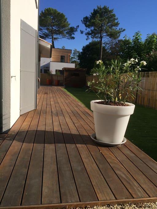 Jardin avec terrasse en bois exotique et pelouse synthétique dernière génération