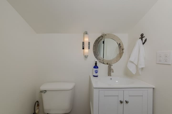 Loft bathroom with toilet sink mirror.