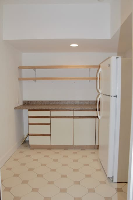 Kitchen area with a microwave , refrigerator , coffee maker . Glasses , cups and dishes .