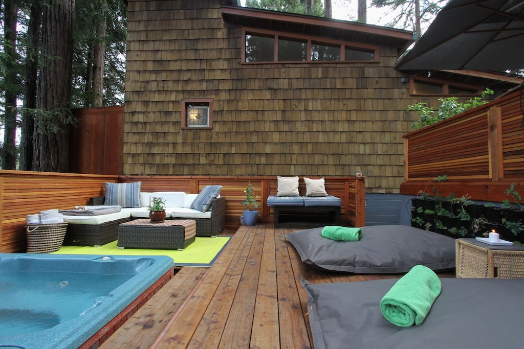 The hot tub with sofa's and 2 queen size bean bag chairs on the back deck