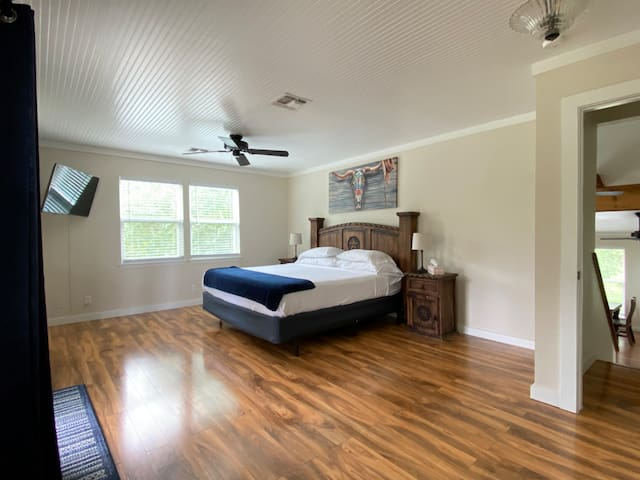 Middle bedroom suite with king size bed, tv and balcony with view of the front yard and street. The bathroom is down the hall.