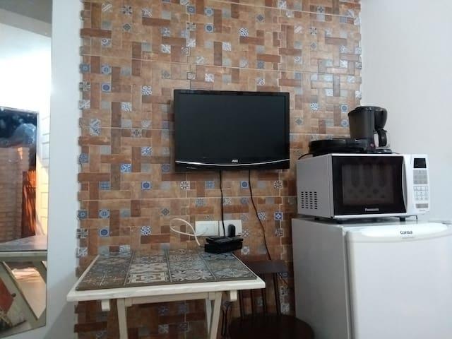 Espaço para pequenas refeições, Misteira, cafeteira, frigobar, microondas.mesa , cadeira. Talheres pratos, copos.